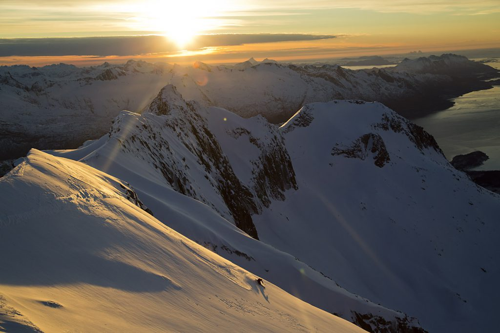 Skier in the sunset, view over the mountains